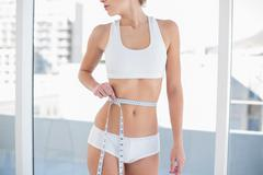 Stock Photo of Close up of a fit woman measuring her waist