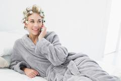 Cheerful relaxed blonde woman in hair curlers calling with her mobile phone - stock photo