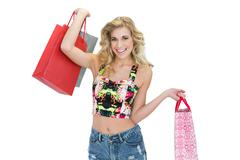 Joyful retro blonde model carrying shopping bags - stock photo