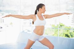 Stock Photo of Smiling fit woman stretching in yoga warrior pose
