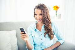 Cheerful model sitting on cosy couch texting Stock Photos