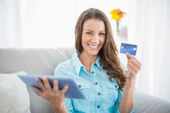 Smiling woman holding tablet and showing her credit card Stock Photos