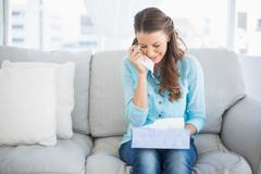 Upset woman crying sitting on sofa Stock Photos