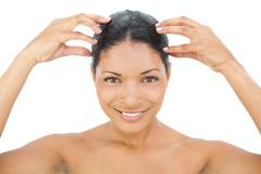 Stock Photo of Smiling black haired model massaging her head