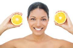 Smiling black haired model holding orange slices - stock photo