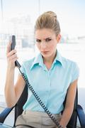 Frowning stylish businesswoman holding the phone Stock Photos