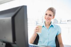 Smiling elegant businesswoman holding coffee - stock photo
