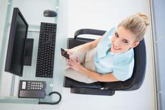 Overhead view of smiling businesswoman text messaging Stock Photos