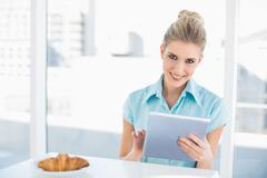 Smiling classy woman using tablet while having breakfast - stock photo