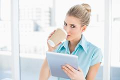 Relaxed classy woman using tablet while drinking coffee - stock photo