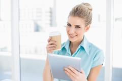 Smiling classy woman using tablet holding coffee - stock photo