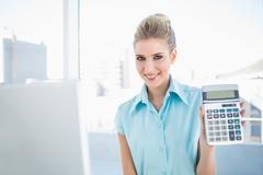 Stock Photo of Smiling elegant woman showing calculator