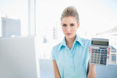 Frowning elegant woman showing calculator Stock Photos