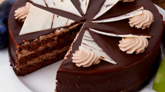 chocolate cream brownie cake layers slice with fruits and big whole cake - stock footage