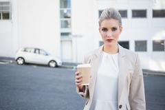 Stock Photo of Serious stylish businesswoman holding coffee
