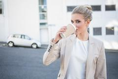 Stock Photo of Cheerful stylish businesswoman drinking coffee