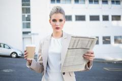 Stock Photo of Serious stylish businesswoman holding newspaper and coffee