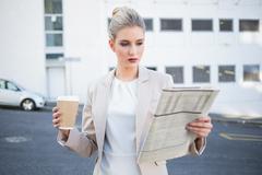 Stern stylish businesswoman reading newspaper - stock photo