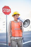 Angry businesswoman wearing builders clothes shouting in megaphone - stock photo