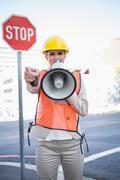Stock Photo of Businesswoman wearing builders clothes screaming in megaphone