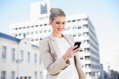 Cheerful attractive businesswoman sending a text message - stock photo