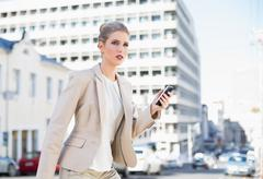 Frowning gorgeous businesswoman text messaging Stock Photos