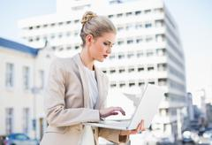 Serious gorgeous businesswoman holding laptop Stock Photos
