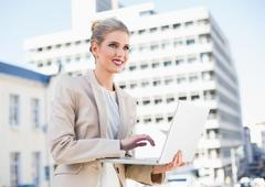Cheerful gorgeous businesswoman working on laptop Stock Photos