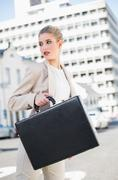 Stock Photo of Serious elegant businesswoman holding briefcase