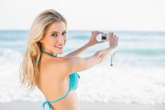 Attractive blonde in bikini taking a self picture looking at camera - stock photo