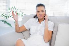 Irritated woman in white dress having a phone call Stock Photos
