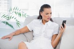 Irritated woman in white dress looking at her smartphone Stock Photos