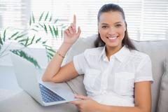 Stock Photo of Happy cute woman using laptop sitting on cosy sofa
