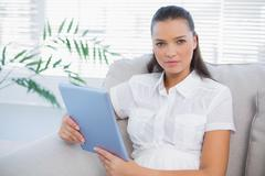 Serious cute woman holding tablet sitting on cosy sofa Stock Photos