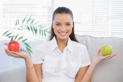 Smiling woman holding red and green apple sitting on sofa - stock photo