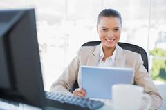 Smiling sophisticated businesswoman holding tablet pc - stock photo