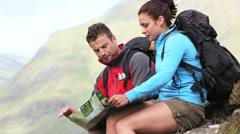 Lost couple sitting on a rock and consulting a map Stock Footage