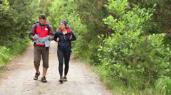 Couple walking along a country trail looking at map Stock Footage