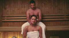 Man giving his girlfriend a neck massage in the sauna Stock Footage