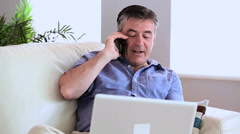 Happy man talking on the phone on the sofa with his laptop - stock footage