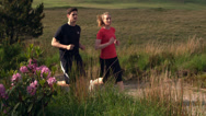 Stock Video Footage of Athletic couple jogging on a country trail