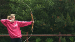 Stock Video Footage of Blonde woman shooting bow and arrow