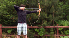 Stock Video Footage of Athletic man shooting a bow and arrow