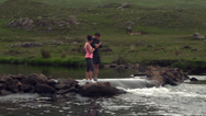 Stock Video Footage of Couple standing on rocks in the middle of a flowing river