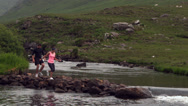 Stock Video Footage of Couple crossing rocks in the middle of a flowing river