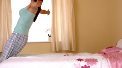 Attractive young woman dropping back on her bed Stock Footage