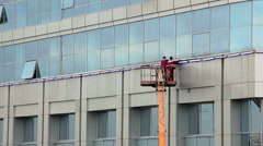 Workers washing windows of building facade standing on lift Stock Footage