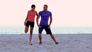Stock Video Footage of Woman stretching and being coached on the beach