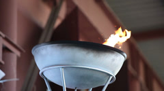 Olympic flame firing in steel bowl Stock Footage