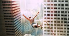 Man Bungee Jumping In City Stock Photos